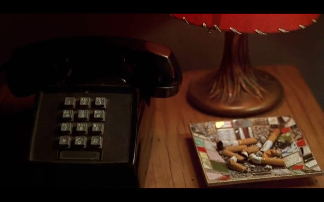 A closeup shoy of a bedstand on which there is a telephone, a lamp, and an ashtray full of butts from American Spirit cigarettes in David Lynch's Mulholland Drive