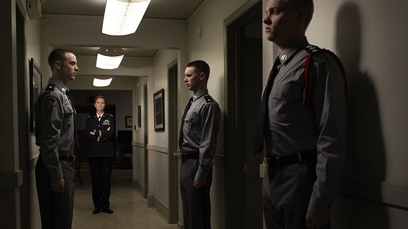 Joan Allen as Margaret Rayne in The Killing standing in a corridor with 3 soldiers standing to attention in her prescence