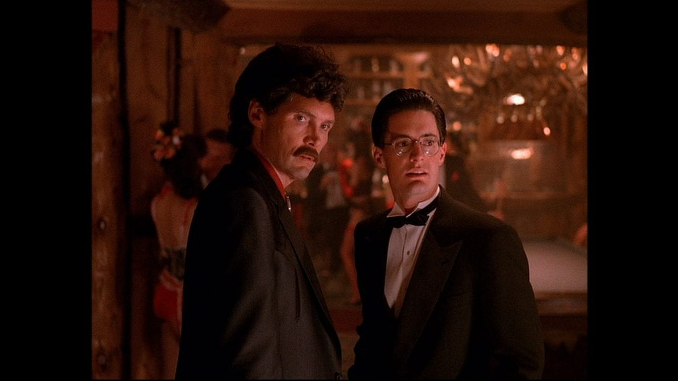 Big Ed wears a curly wig and moustache, Agent Cooper wears a Tuxedo