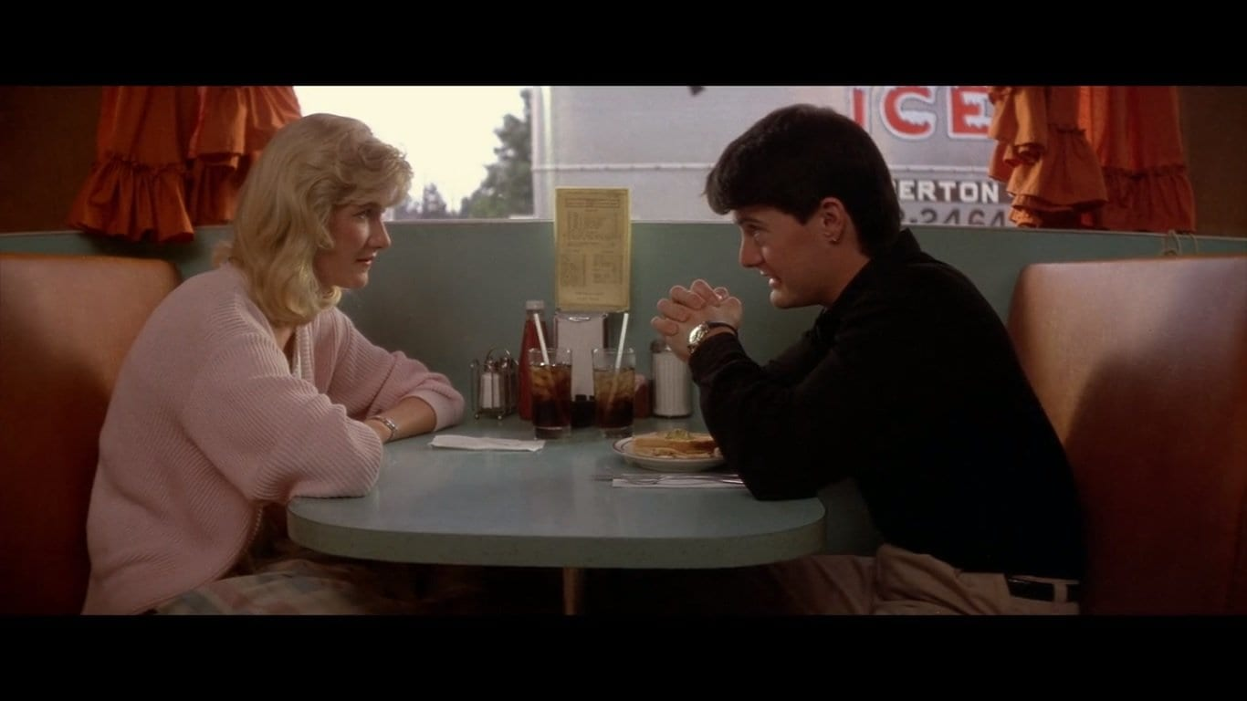 Kyle MacLachlan  as Jeffrey in Blue Velvet sitting in a diner opposite Sandy played by Laura Dern