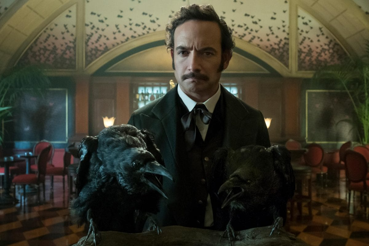 Poe standing in front of two ravens