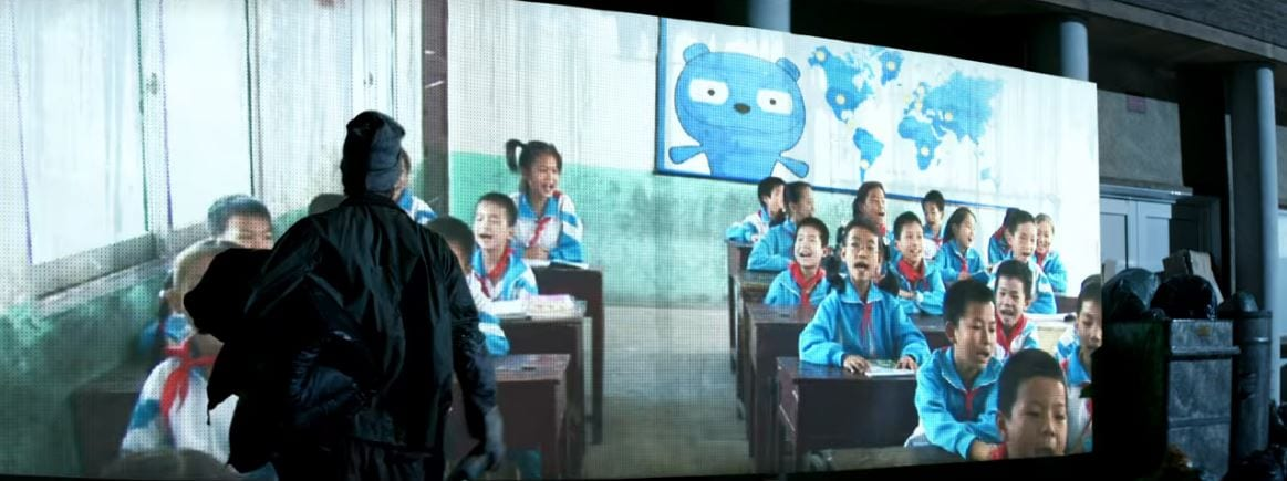 Asian children in a classroom with Waldo on a screen