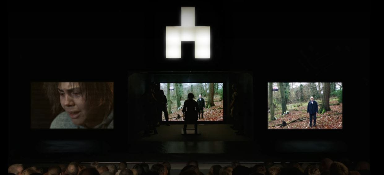 Victoria sits in front of three screens on stage with the White Bear symbol above