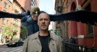 Birdman flies behind Michael Keaton on the street