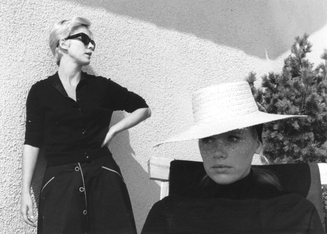 a blonde woman stands against a wall wearing shades. Another woman sits in a chair wearing a sun hat