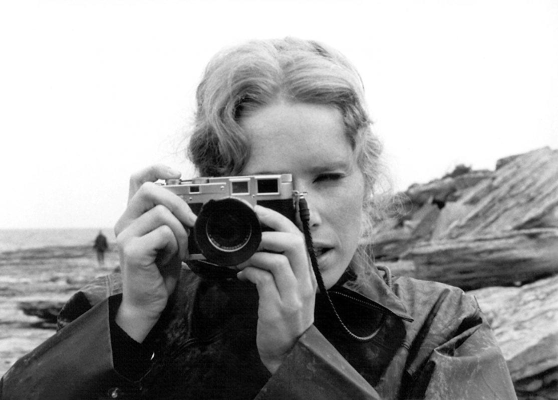 a woman takes a photograph on the beach in Ingmar Bergman's Persona