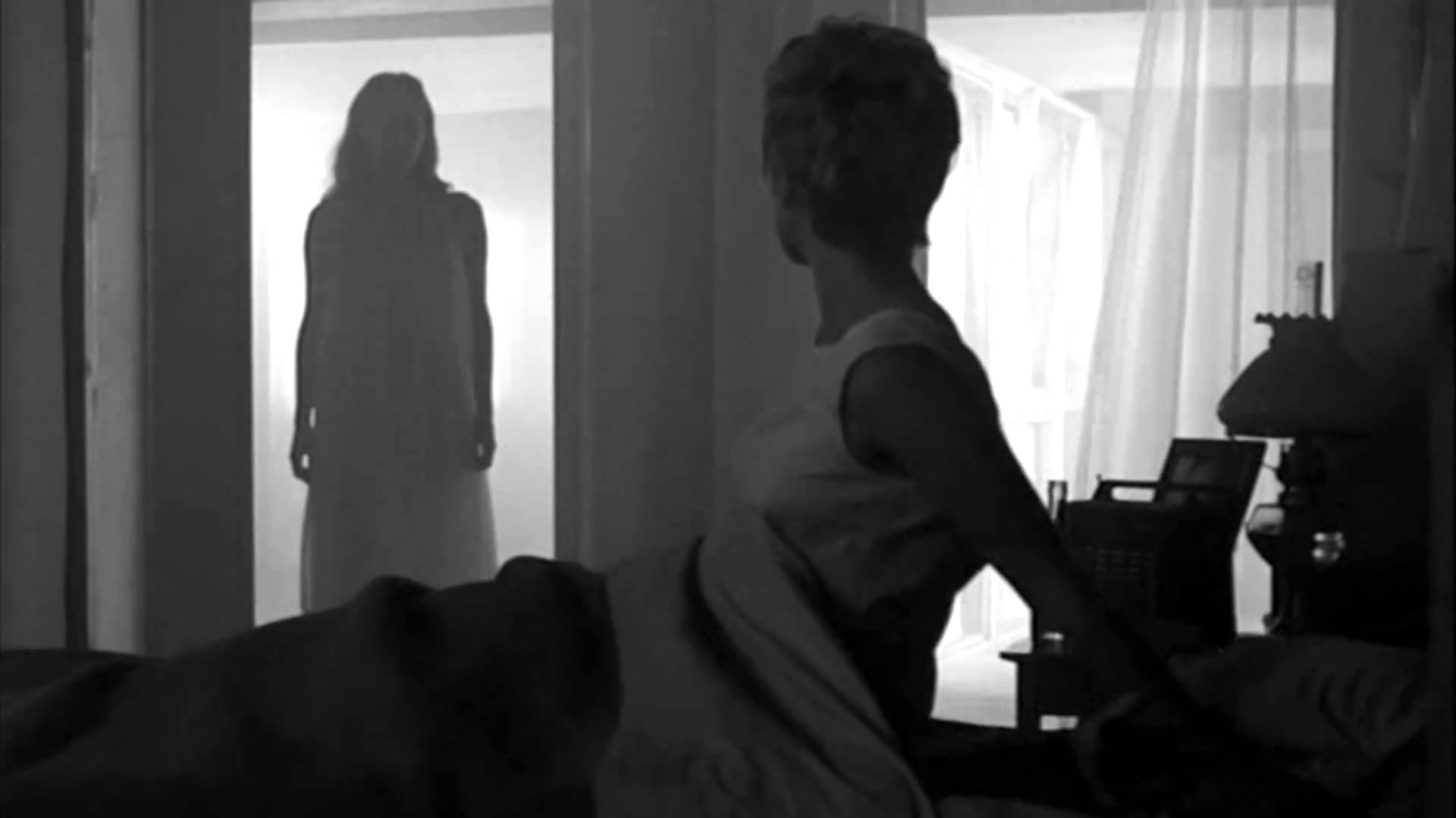 a woman sits upright in bed and sees a female figure looming in her bedroom doorway