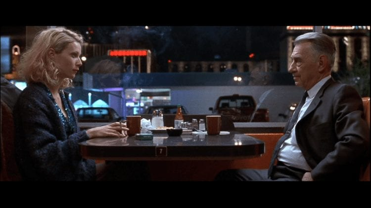 Phillip Baker Hall and Gwyneth Paltrow sit opposite each other in a diner at night in Hard Eight