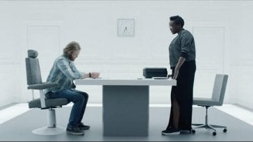 """Cooper sits at a white table as he prepares to play a game for Katie in Black Mirror """"Playtest"""""""