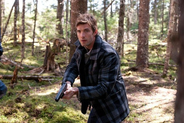Lucas Bryant stalks the woods with a gun in his hand