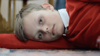A young Leland lies in the floor wearing a red sweater