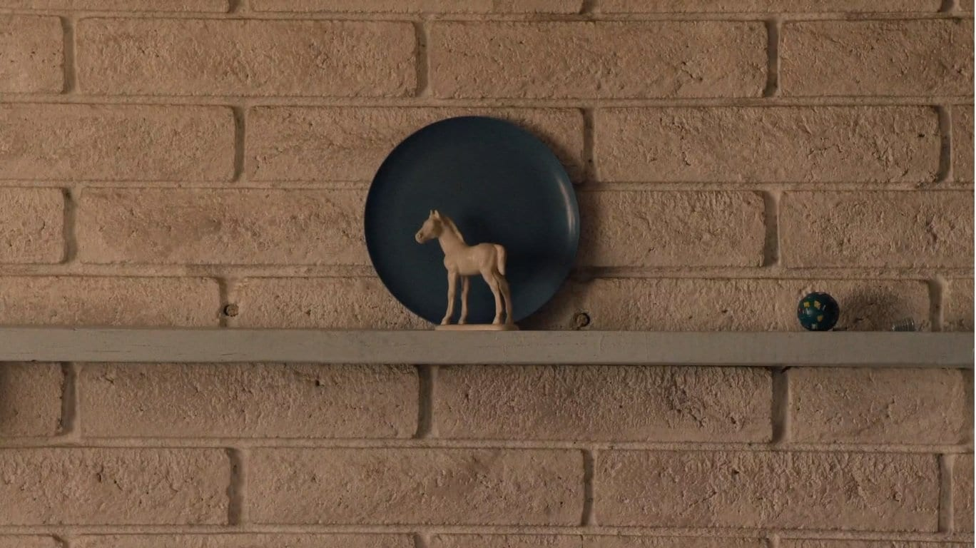 a blue plate against a white wall with a white horse figurine