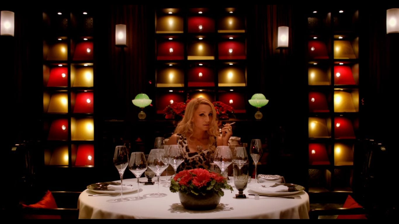 Nicolas Winding Refn's Bronson, a woman sits at a table in a restaurant smoking an looking sexually provocative