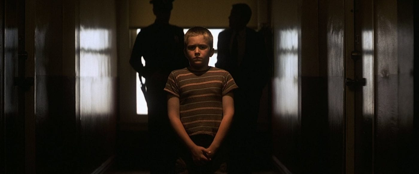 a young boy in a striped shirt stands in a hallway with two cops behind him looking upset