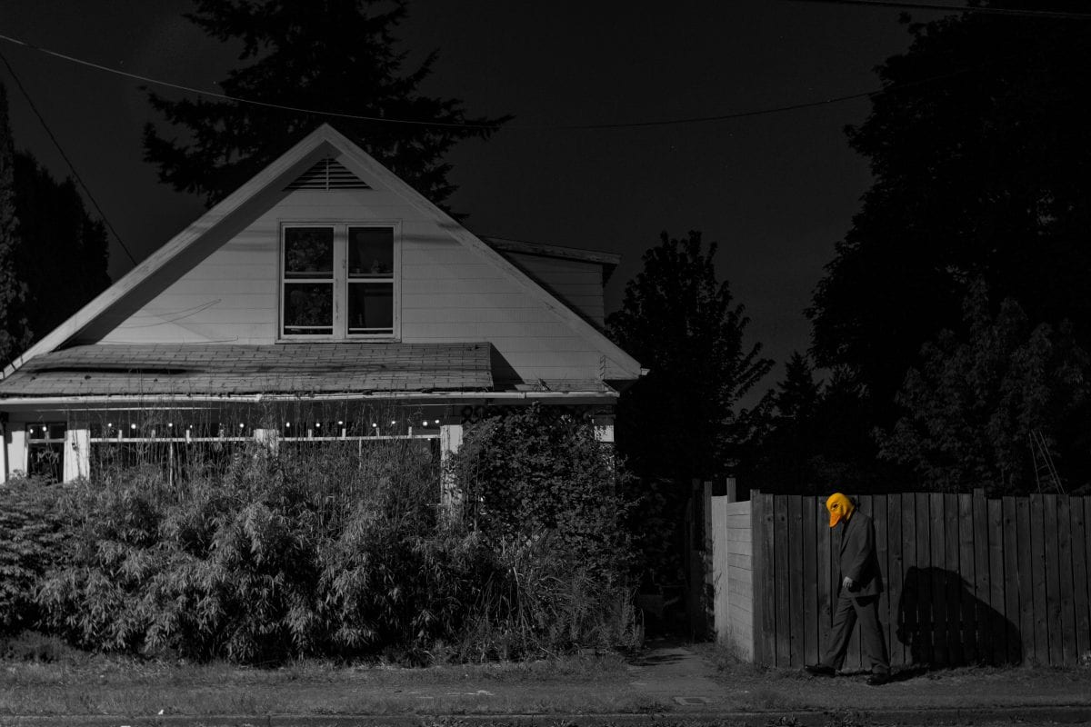 a duck man walking outside a house