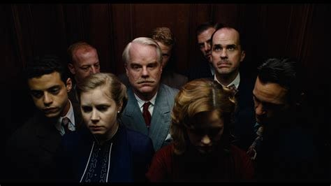 a group of people stand silently in an elevator in The Master