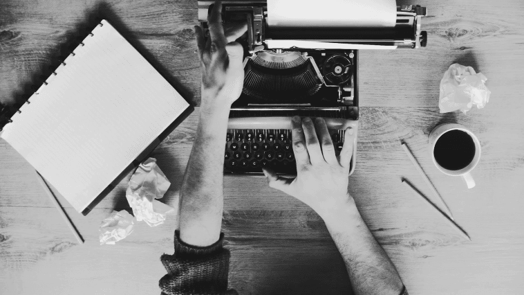 Two hands on a typewriter in a black and white photo