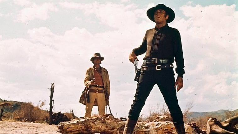 a cowboy goes for his gun as another points his towards him