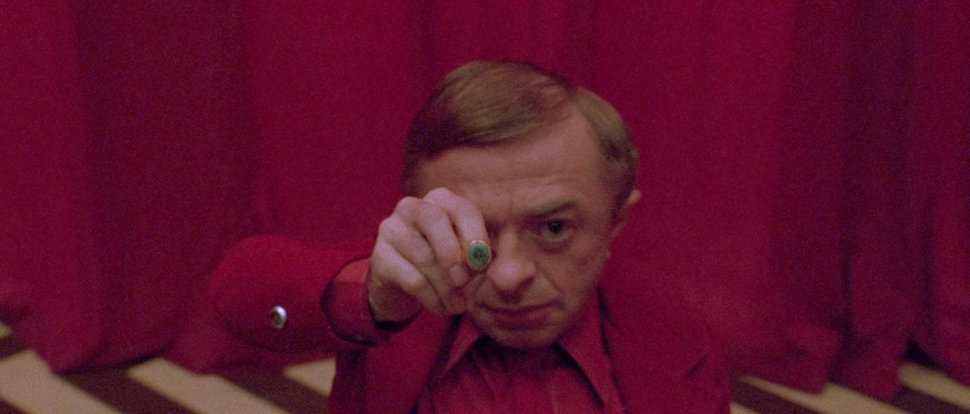 The Arm/Man From Another Place holds the owl cave ring out in front of his face in the Red Room in Twin Peaks