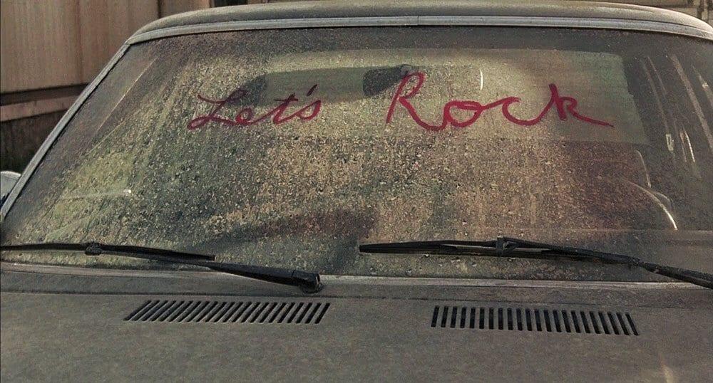Let's Rock written in lipstick on a dirty car windscreen
