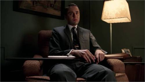 Pete Campbell sits in a chair looking angry with a shotgun primed in his lap