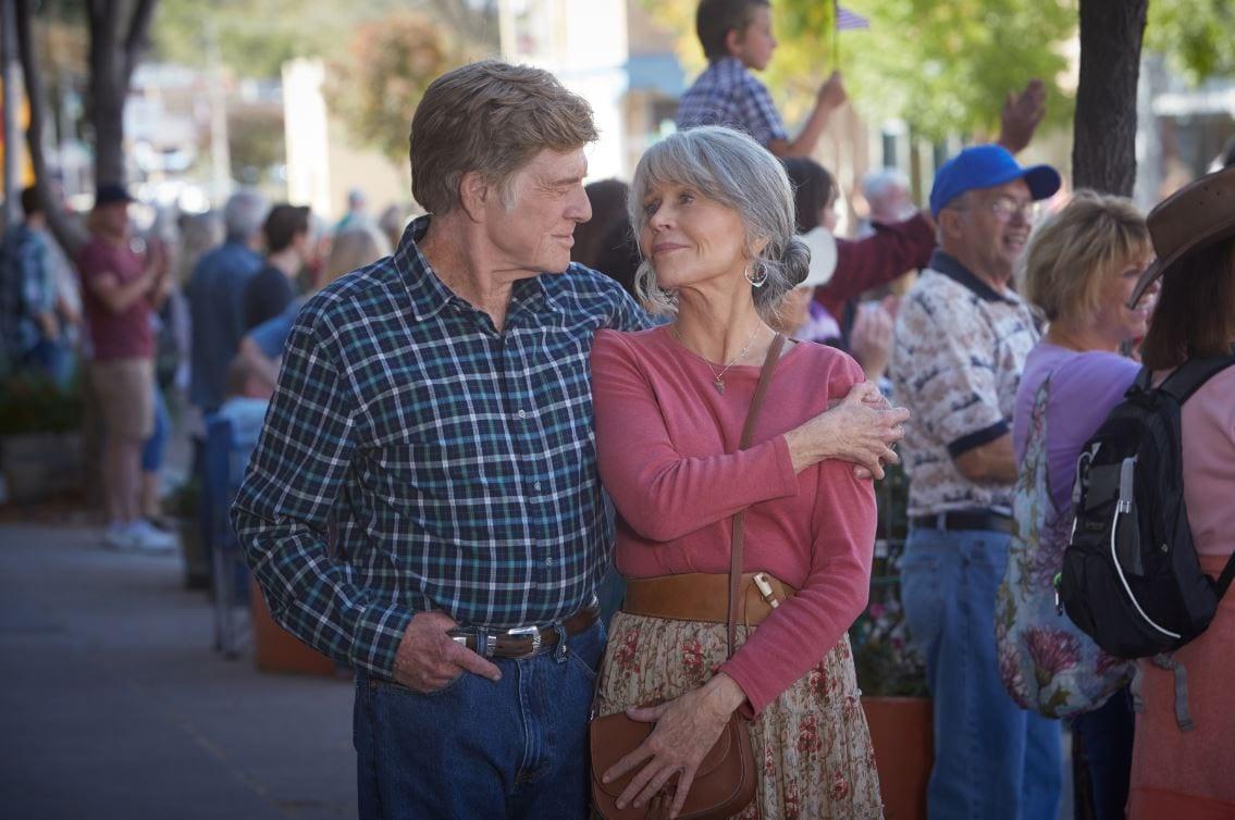 Robert Redford and Jane Fonda walk arm in arm down a street