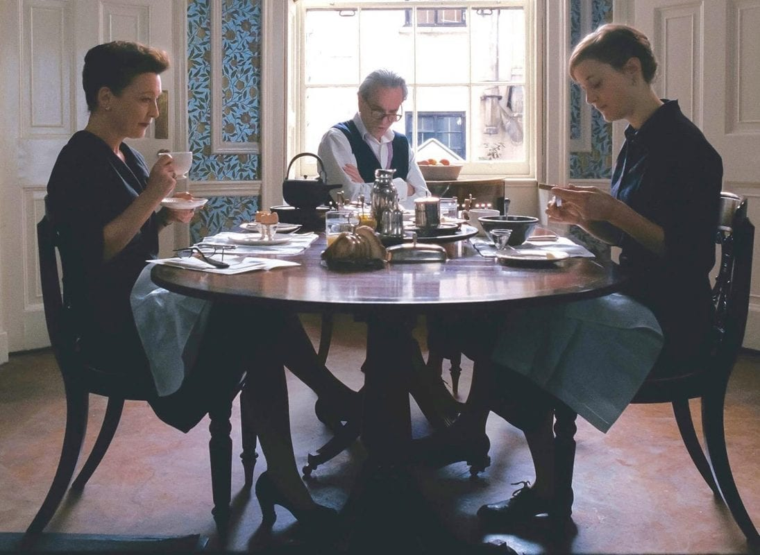 a woman and her parents sit at a dining table drinking tea very formally