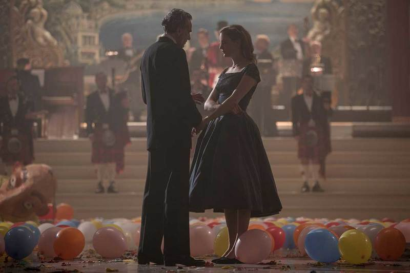 a male and female at the end of a party, balloons scattered at their feet and a band wearing kilts behind them