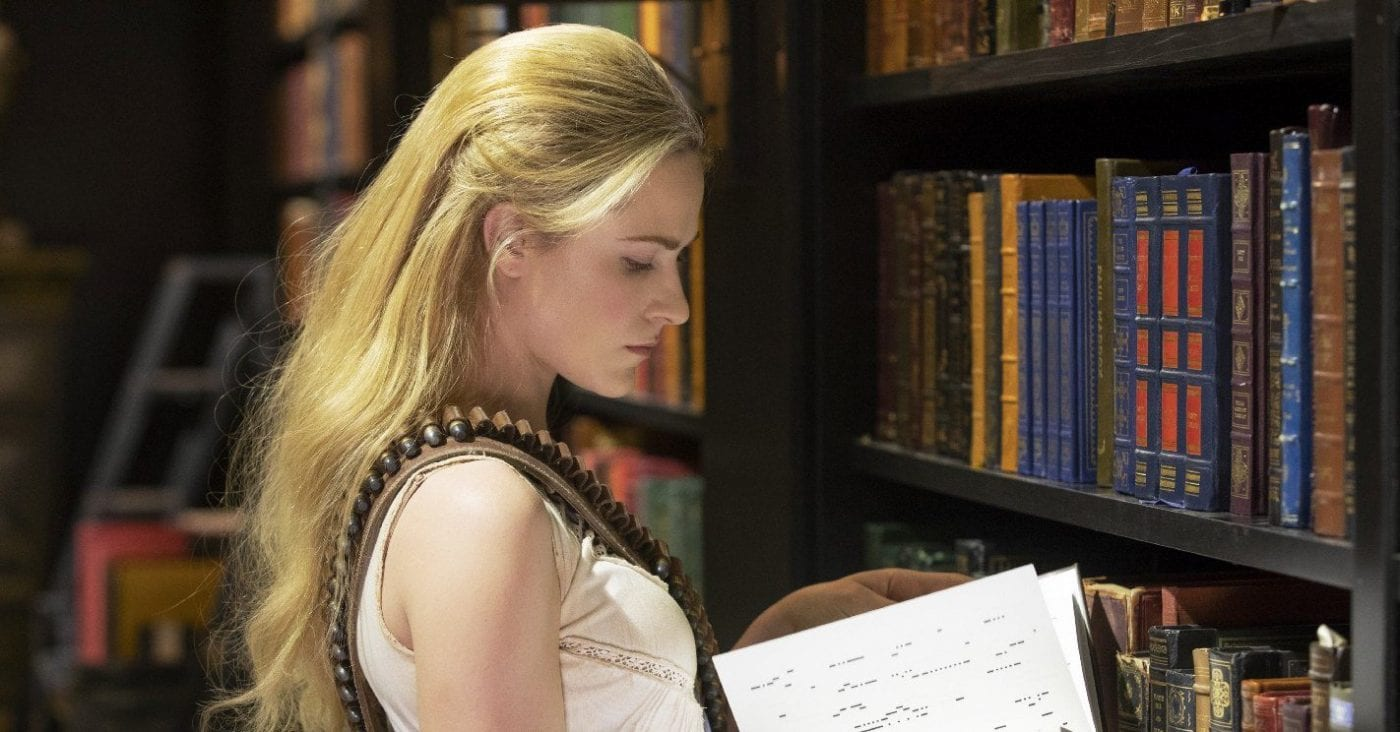 Dolores looks at a book in library within the Forge