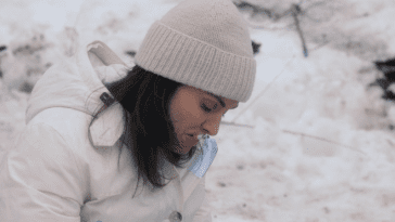 Laurie, dressed in all white, smokes a cigarette with snow in the background