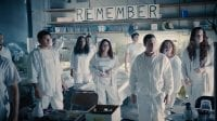 """Members of the Guilty Remnant are dressed in white standing in a room with """"remember"""" up on the wall behind them"""