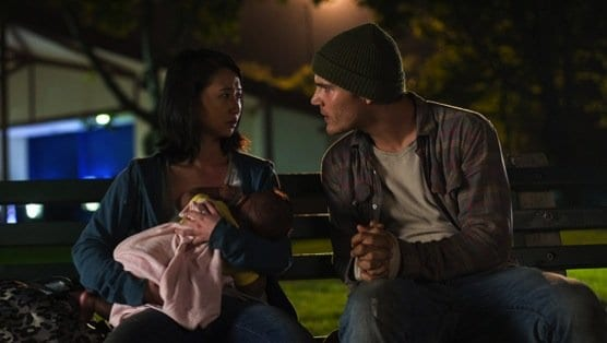 Tommy sits on a bench with Christine and her baby, pleading with her