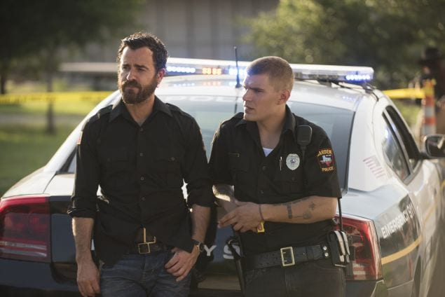 Tommy leans against a cop car with his dad, Kevin, in a police uniform