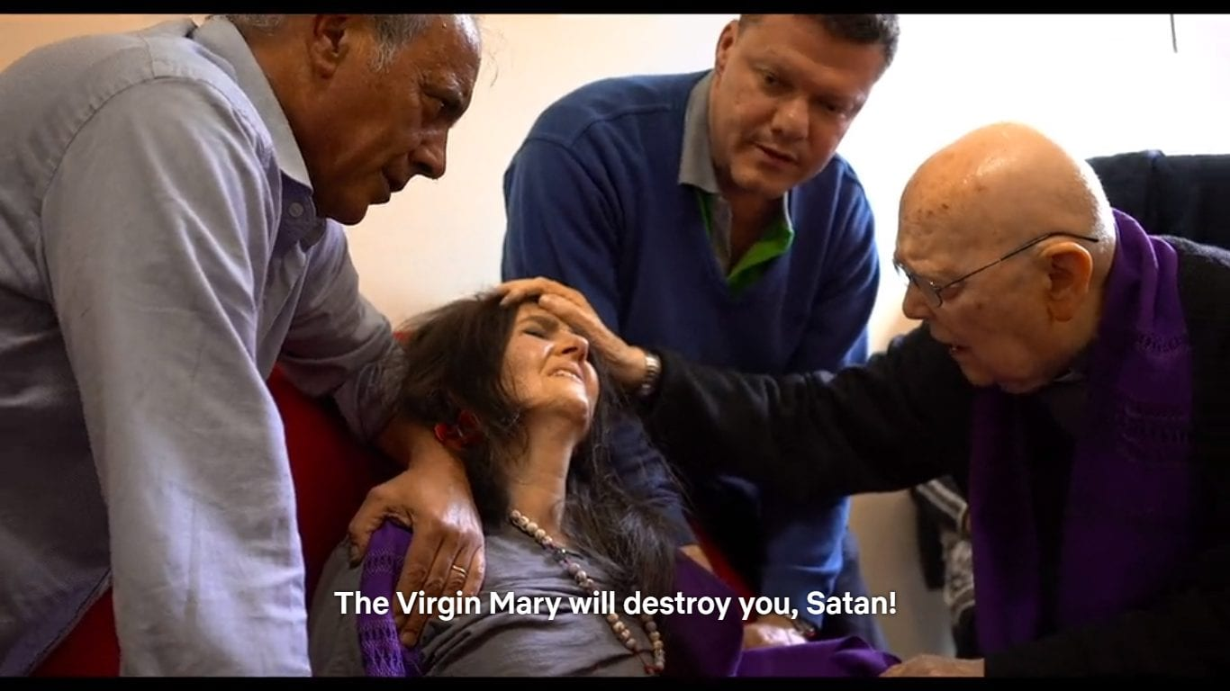 3 men hold a woman down as she is exorcised by Father Amorth
