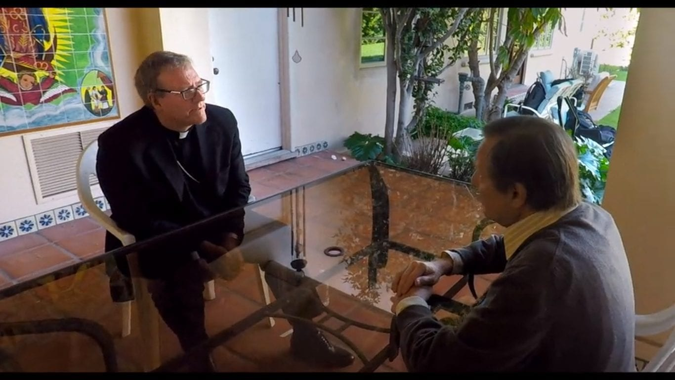 A priest talks to Father Amorth over a glass table