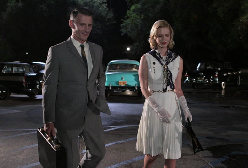 Betty and Henry walk through a car park together at night, smiling