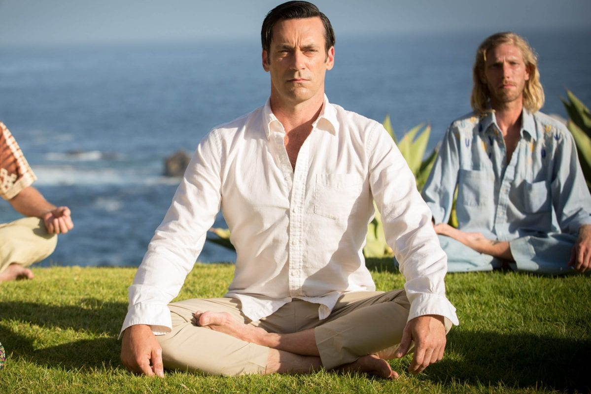Don Draper sits cross-legged doing yoga on the grass