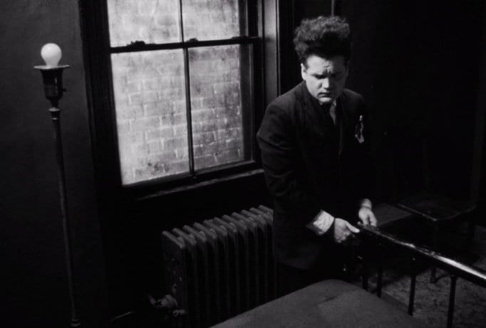 Henry Spencer looks nervously towards a bed in Eraserhead