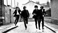 The Beatles running down a street