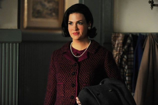 betty draper with dark hair, extra weight after learning she has cancer, but is smiling