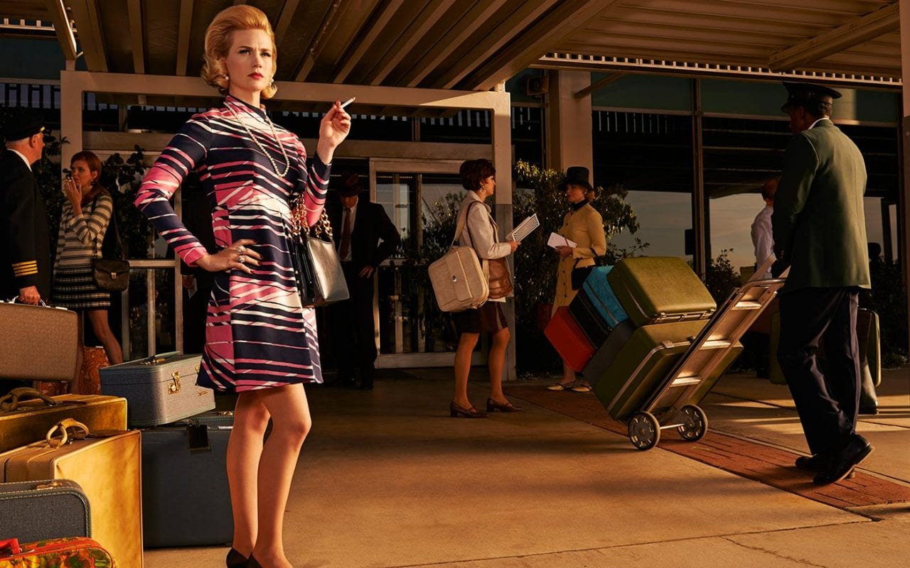 betty draper smokes a cigarette while standing by hoards of luggage at a posh hotel