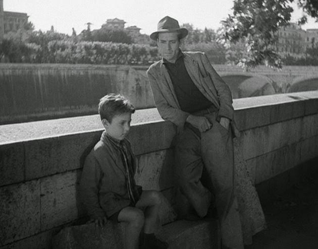 a boy sits and a mean leans against a bridge over a river