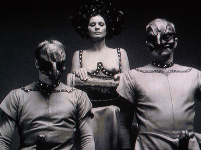 2 men in strange masks and a woman with breasts exposed