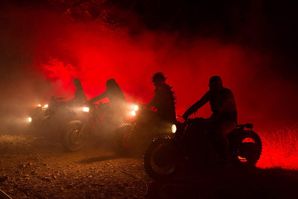 The Black Skulls on motorbikes lit by red light in Mandy