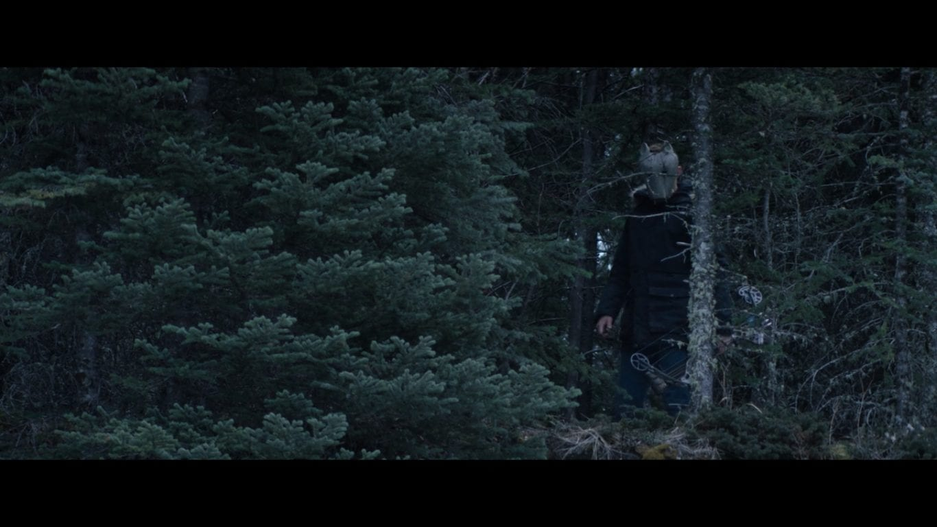 a masked man lurks in the trees in Hold the Dark