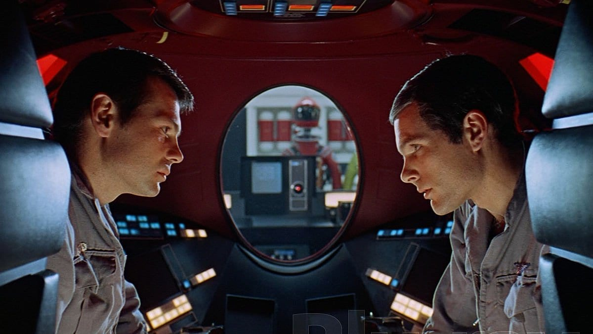 Astronauts look at each other in front of an oval window in 2001