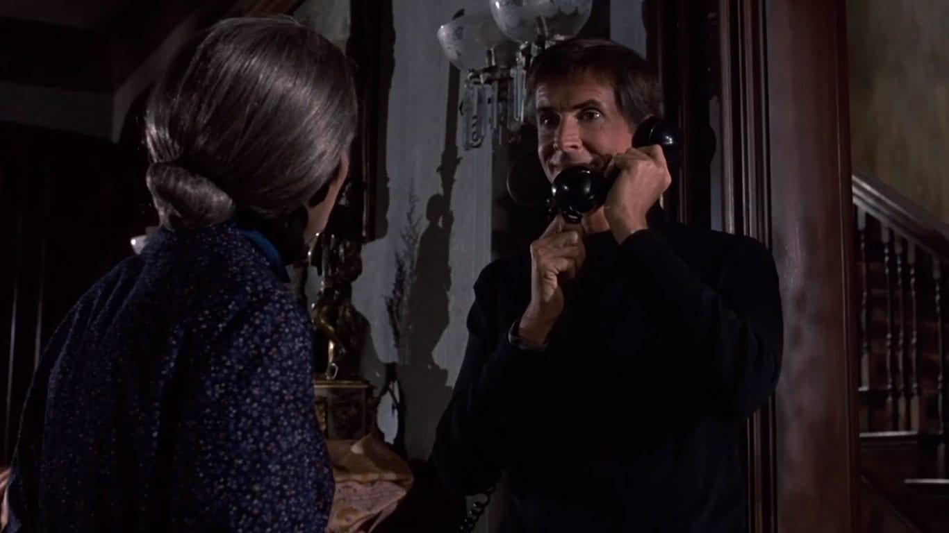 Norman Bates talks on the phone with a smile