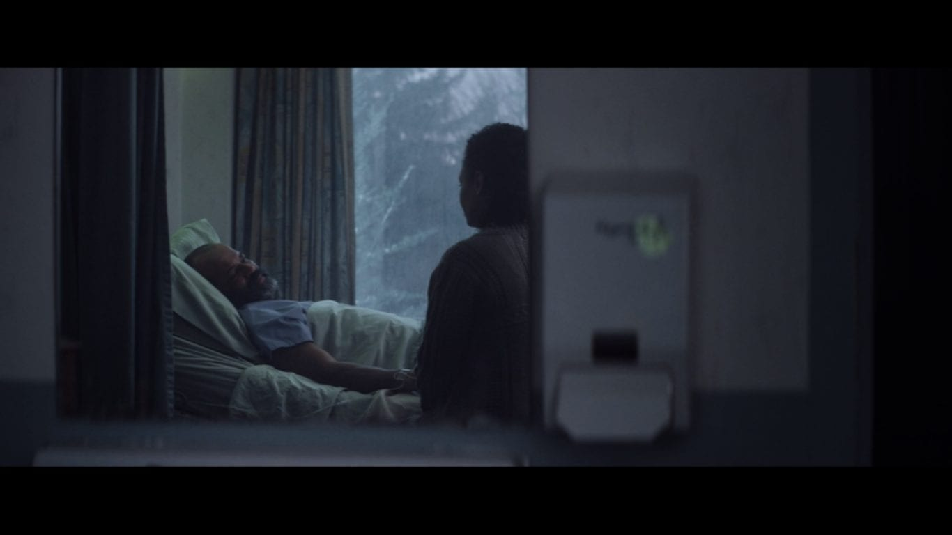 a man lies in a hospital bed with a woman at his side