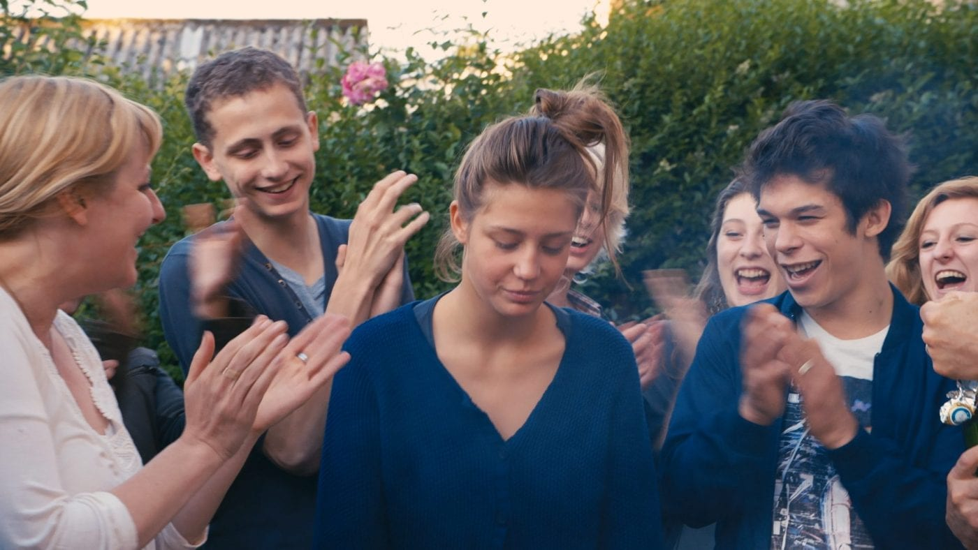 Adèle Exarchopoulos as Adèle being clapped by a crowd of people laughing in Blue Is the Warmest Colour