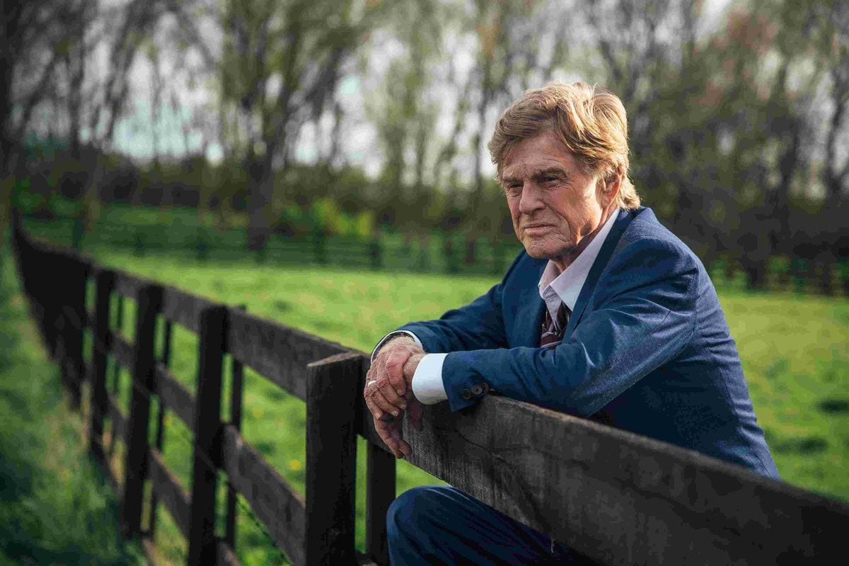 Robert Redford as Forrest Tucker holding on to a fence in a field